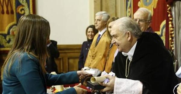 Elena Herrera enseña la tarjeta de embarque al rector de la Universidad de Oviedo